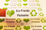 Close up of eco friendly packaging rectangular sticker with green heart and recycling icon made from recycled paper
