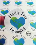 Close up of Plastic Free Packaging click and go sticker with blue and green heart earth design made from recycled paper