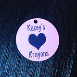 Close up of white and black Kacey's Krayons small round swing tag with black love heart design and 5mm round hole