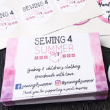 Pack of Sewing 4 Summer multicoloured standard business cards with Facebook and Instagram handle and black and pink logo on a sheet of stickers behind