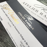Close up of Atelier Rahman bespoke tailoring gold foiled gift voucher  printed on supersmooth white card on a dark blue background including gift voucher information and website address