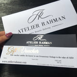 Voucher and envelope Atelier Rahman bespoke tailoring gold foiled gift voucher  printed on supersmooth white card on a dark blue background including gift voucher information and website address