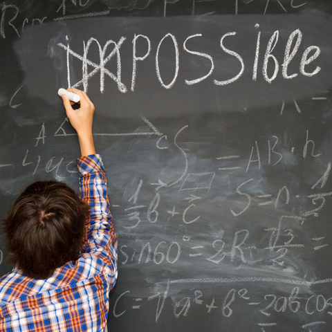 Child writing 'Possible' on a chalk board