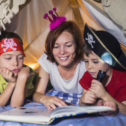 Kids reading under a tent