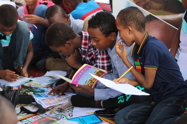 Kids reading from a book together
