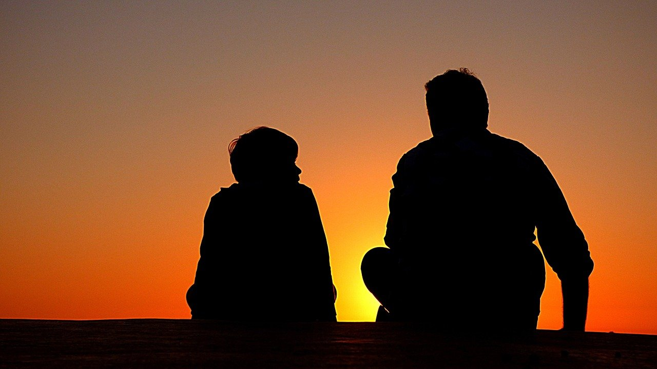 Silhouette of parent and child talking
