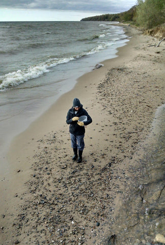 woman beach combing for natural pigment materials