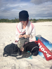 Knit Me owner Kelsi knitting on the beach