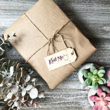Load image into Gallery viewer, Picture of a package wrapped up with brown paper and string representing the Wonderland subscription box