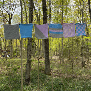 set of the knitted dishcloths hanging on a clothes line