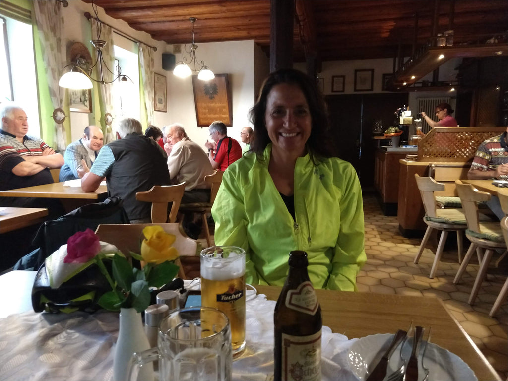 Photo of Maria smiling in a cozy restaurant with beer on the table in Bavaria