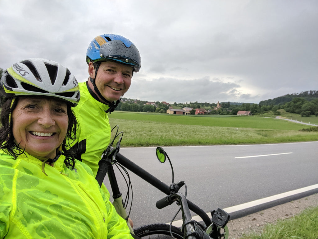 Photo of Jim and Maria grinning despite the rain in the beautiful Bavarian countryside