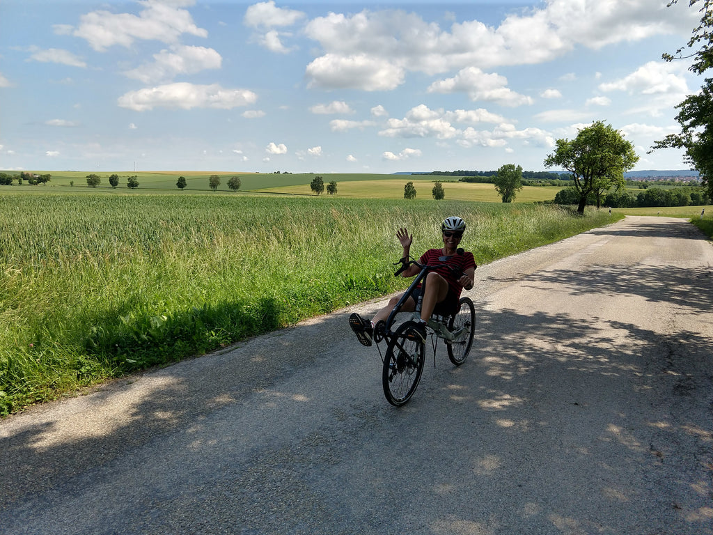 Photo of Maria waving from her Cruzbike Q45 adventure touring recumbent bike in the Bavarian countryside