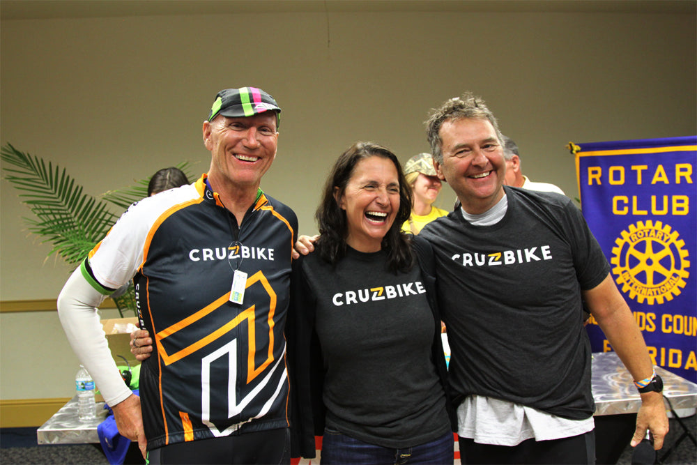 Cruzbike's CEO, Maria Parker, flanked by rival CEOs both wearing Cruzbike colors.