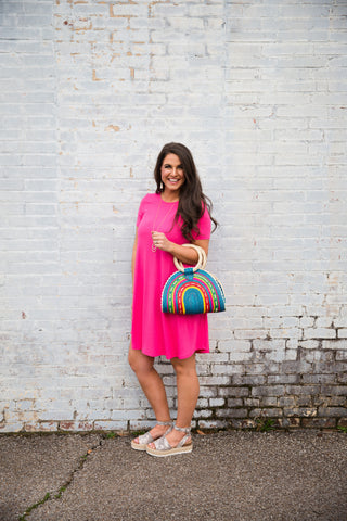 Carey, the owner of Carey's Boutique, standing in front of a white brick wall in a pink dress holding a multicolor straw handbag.