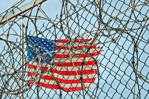 American flag flying behind a fence topped with barbed wire.