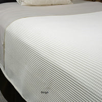 Bed made with beige waffle supreme coverlet.