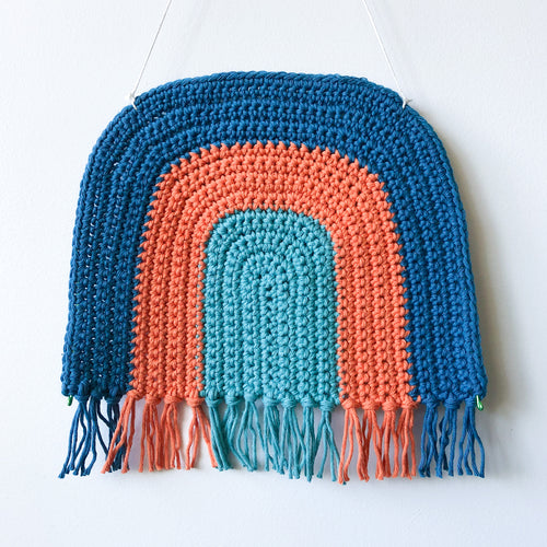 rainbow crochet art by Pikki Nikki hanging on a wall featuring a variety of colours