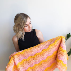 Nikki holds a crochet Making Waves blanket featuring mustard, peach, and pink colours