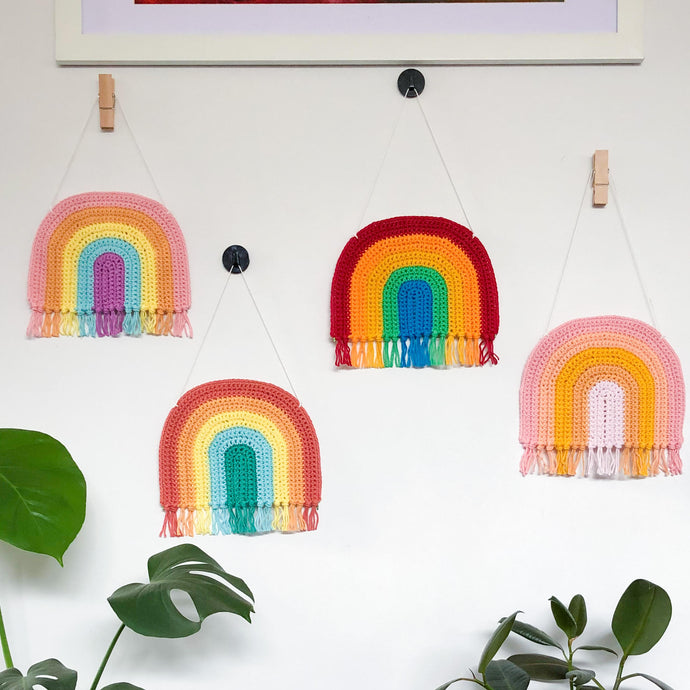 rainbow crochet art hanging on a wall featuring a variety of colours