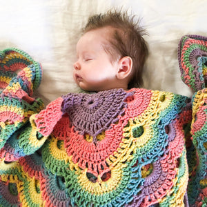 Baby girl lays sleeping wrapped in handmade crochet blanket with bright rainbow colours