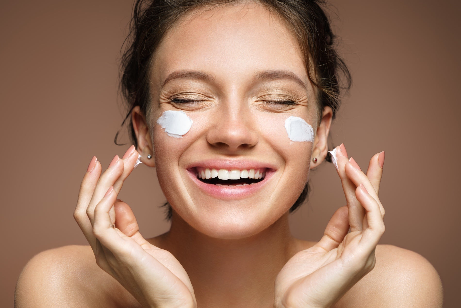 Woman smiling while applying face cream