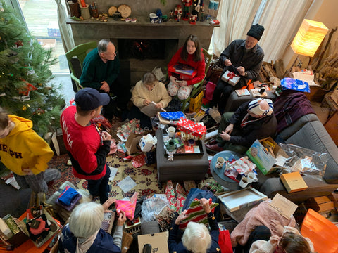 A photo of a family gathered around a Christmas tree opening presents