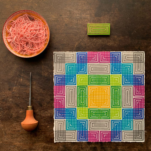 a photo of a brightly-colored geometric print on paper on a dark wood surface with a carving tool, the rectangular print block and a dish of carving scraps.