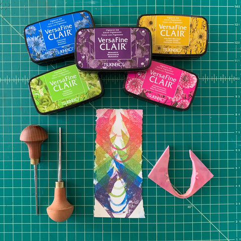 A colorful block print of curved shapes accompanied by colorful stamp pads and carving tools.