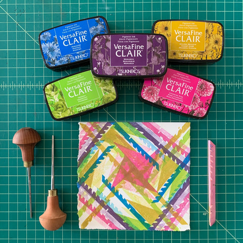 A flatlay of a multicolored square print, accompanied by colored stamp pads and carving tools.