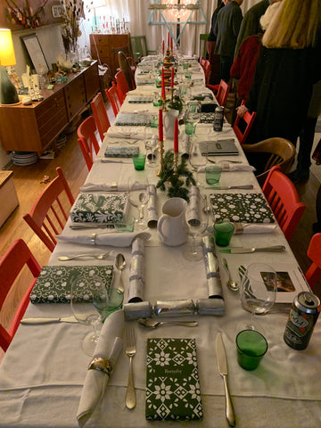 A long Christmas Table ornately and colorfully set with people gathered in the background