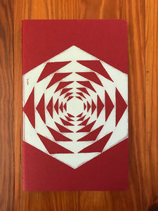 Hand block printed Moleskine Medium ruled chair journal in red. Printed in white ink on a geometric pattern.