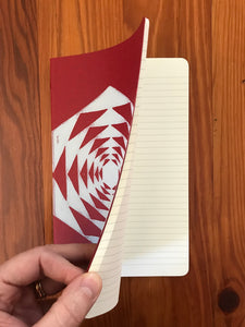 Hand block printed Moleskine Medium ruled chair journal in red. Printed in white ink on a geometric pattern. Shown open to display that it is ruled.