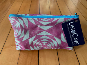 A light green and magenta zipper pouch with a turquoise zipper. Hand block printed with a geometric pattern.