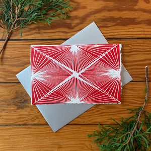 "A hand block printed 4""x6"" card with red ink on white paper. Features a fine-line design. An A4 metallic silver envelope is placed behind it. It is surrounded by greenery on a distressed wood background."