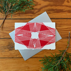 "A hand block printed 4""x6"" card with a fine-lined design in a four-pointed star shape. Red ink on white paper. A A4 metallic silver envelope is placed behind it. It is surrounded by greenery with a distressed wood background."