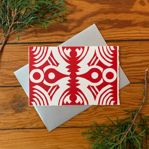 "A hand block printed 4""x6"" greeting card with a bold circular design with red ink on white paper. A metallic silver A4 envelope is place behind it and it is surrounded by greenery on a distressed wood background."