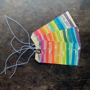 Set of three hand block printed rainbow manila gift tags.