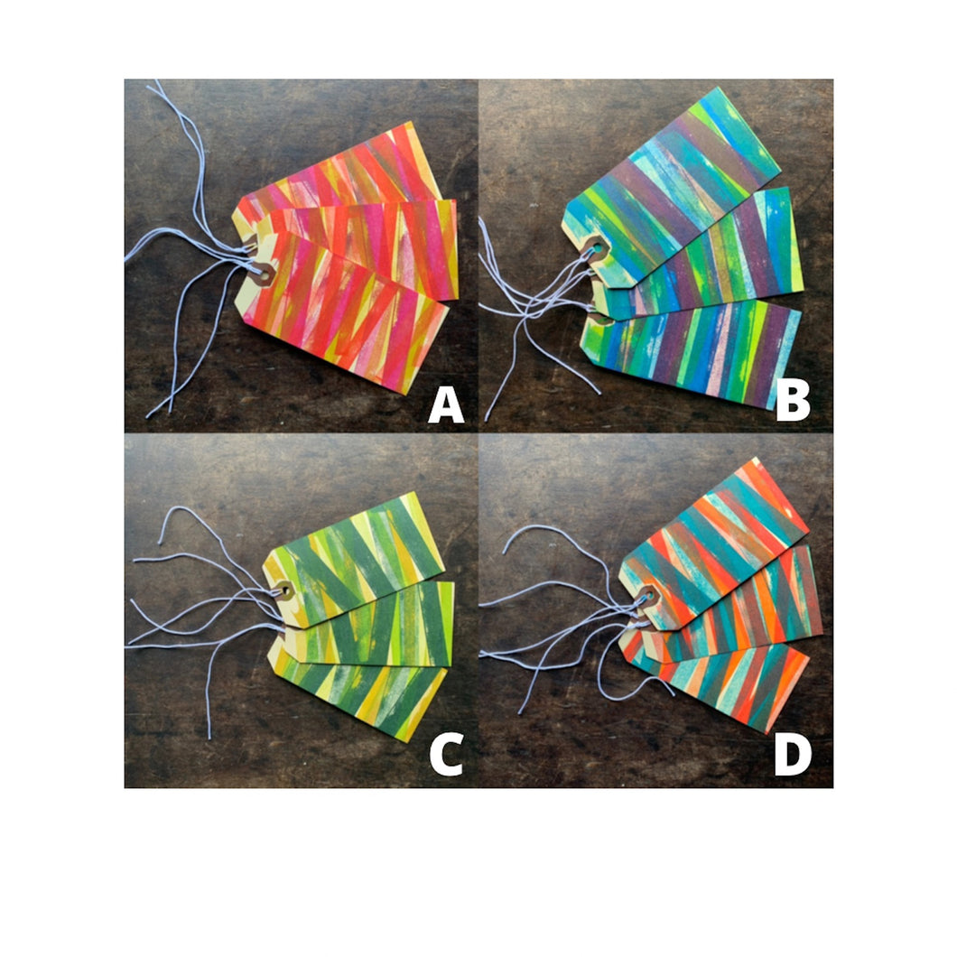 A four-panel of sets of three manila gift tags in multicolored striped patterns in different bright color ways.