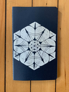 A medium navy Moleskine journal hand printed with a geometric pattern with white ink.