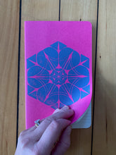 Load image into Gallery viewer, A medium pink Moleskine journal hand printed with a geometric pattern with blue ink. Open to show it is ruled.