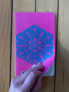 A medium pink Moleskine journal hand printed with a geometric pattern with blue ink. Open to show it is ruled.