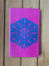 Load image into Gallery viewer, A medium pink Moleskine journal hand printed with a geometric pattern with blue ink.