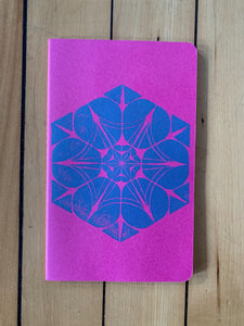 A medium pink Moleskine journal hand printed with a geometric pattern with blue ink.