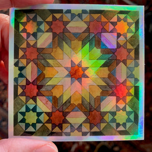 "A photograph of a 3"" holographic sticker which has a ""Moroccan Rosettes"" pattern on it in a blend of colors and neutrals."
