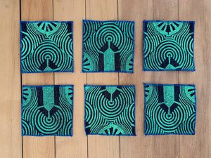 A set of six denim coaters hand block printed in a green geometric design with a blue rolled edge hem.