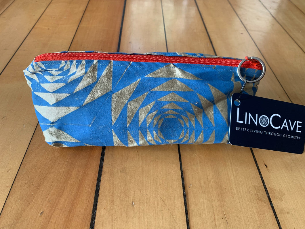 A warm beige and blue silk pencil case by LinoCave. Has a dark orange zipper.