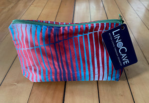 A red silk toiletry bag with a dark green zipper hand block printed with an ombre of colors ranging from light to dark blue.