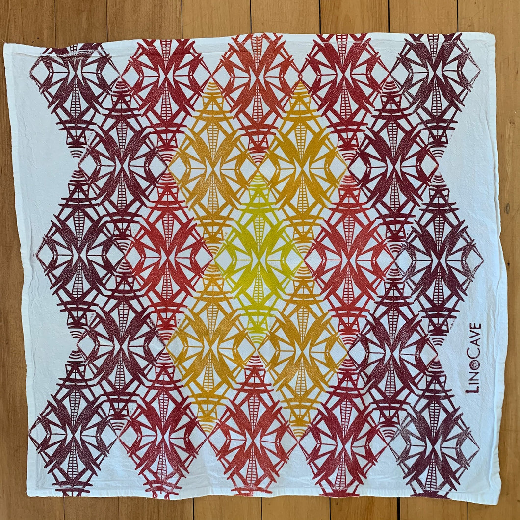 A hand block printed white flour sack towel with am ombre of warm colors in a geometric pattern.