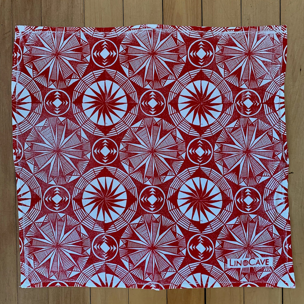 A hand block printed white flour sack towel with red in a geometric pattern.